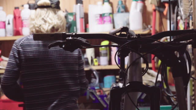 a young man working alone on repairing a bike in his home garage workshop, social distancing. - repairing stock videos & royalty-free footage