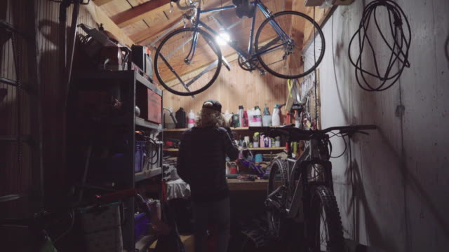 a young man working alone on repairing a bike in his home garage workshop, social distancing. - equipment点の映像素材/bロール
