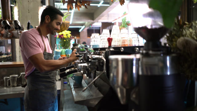 young man working at a cafe making a cappuccino looking focused - bar area stock videos & royalty-free footage