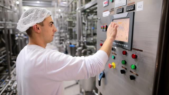 vídeos y material grabado en eventos de stock de joven trabajando en una fábrica de alimentos en la estación de control. de la mano en la pantalla táctil - operar
