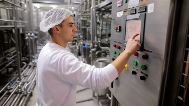 young man working at a food factory on the control station.hand on the touch screen - dairy factory stock videos & royalty-free footage