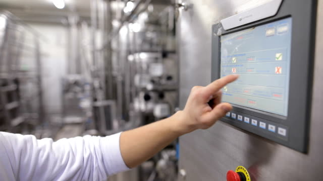 young man working at a food factory on the control station.hand on the touch screen - pannello di controllo video stock e b–roll