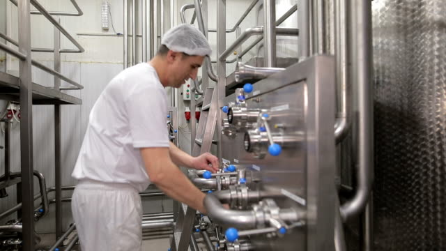 young man working at a food factory. - dairy factory stock videos & royalty-free footage