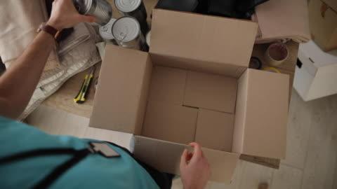 giovane che lavora presso fondazione di beneficenza, scatola di imballaggio donazione - volunteer video stock e b–roll