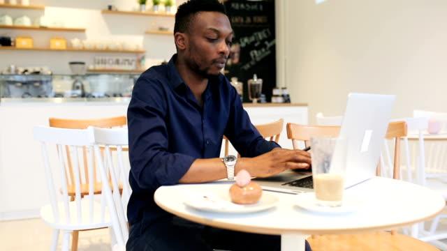 vidéos et rushes de jeune homme travaillant dans le café-bar - un jour comme les autres images en série