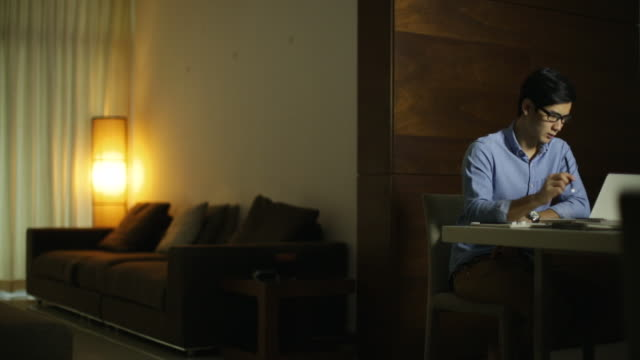 vídeos de stock e filmes b-roll de ws young man working late at home. - lâmpada elétrica