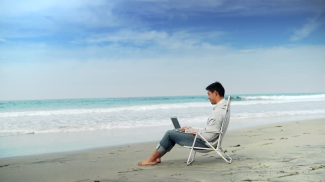 WS Young man working on a laptop by the ocean