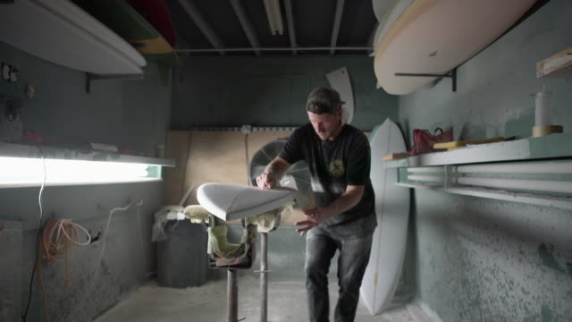 stockvideo's en b-roll-footage met ms young man working on a surfboard in his workshop - kunstenaar