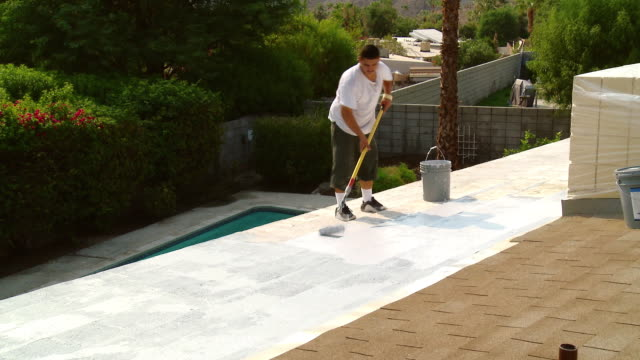 WS Young man working on concrete shingled patio roof / Rancho Mirage, California, USA.