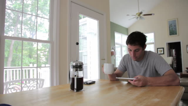 MS Young man working on digital tablet at kitchen table / Lorton, Virginia, United States