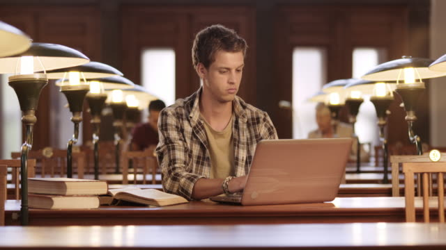 ds young man working on his laptop in the library - study stock videos & royalty-free footage