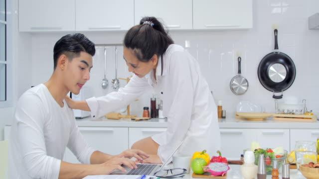 vídeos y material grabado en eventos de stock de joven trabajando en ordenador portátil en la cocina como novia prepara comida. pareja multirracial feliz relación sana - happy meal
