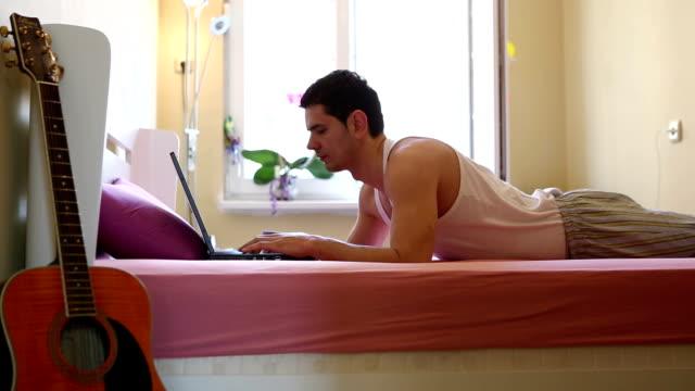 vidéos et rushes de jeune homme travaillant sur ordinateur portable - seulement des jeunes hommes