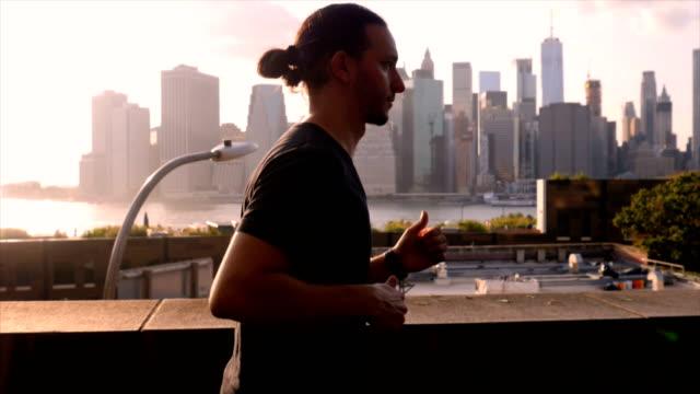 junger mann gegen die new york city waterfront sonnenuntergang trainieren - kamerafahrt auf schienen stock-videos und b-roll-filmmaterial