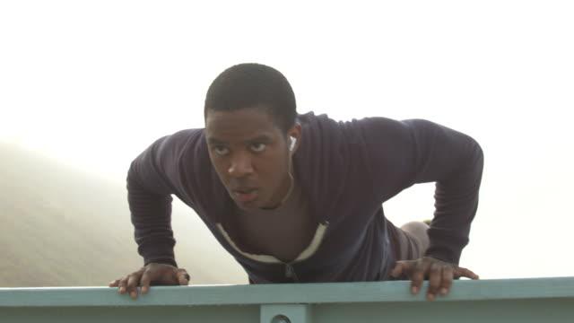 vídeos de stock e filmes b-roll de a young man working out and doing push ups on the beach. - flexão de braço