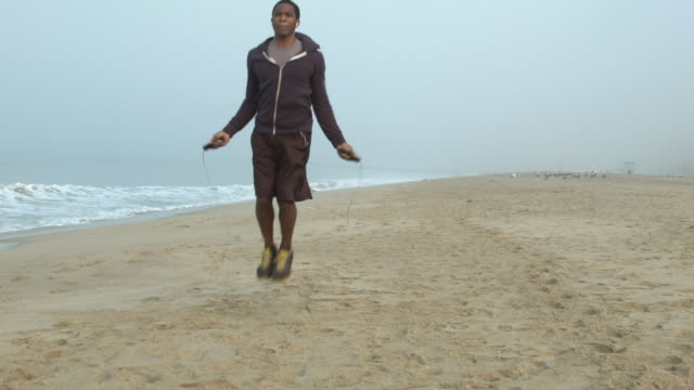a young man working out and jump roping on the beach. - goodsportvideo stock videos and b-roll footage