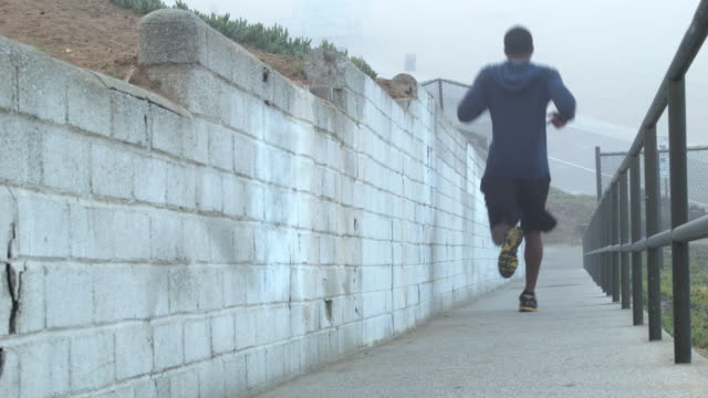 a young man working out and running on a steep ramp by the beach. - goodsportvideo stock videos and b-roll footage