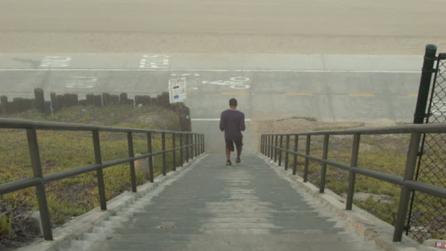 a young man working out and running stairs by the beach. - goodsportvideo stock videos and b-roll footage