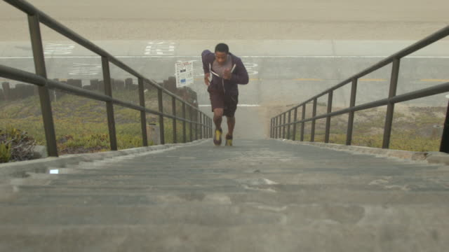 vídeos de stock e filmes b-roll de a young man working out and running stairs by the beach. - passos