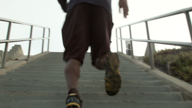 A young man working out and running stairs by the beach.