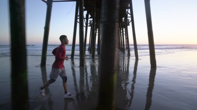 ws young man working out at the beach at sunset. - jogging stock videos & royalty-free footage