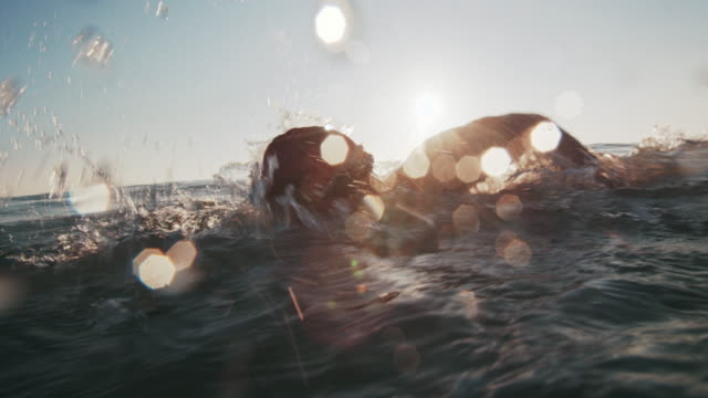 sm cu young man working out in the ocean at sunset - lens flare stock videos & royalty-free footage