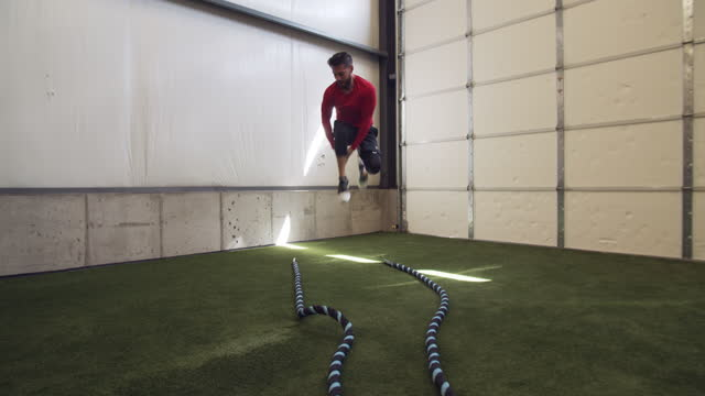 young man working out with heavy ropes at a gym - pull out camera movement stock videos & royalty-free footage