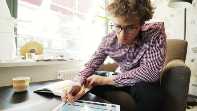 vídeos y material grabado en eventos de stock de hombre joven con una tableta digital y un cuaderno de trabajo. - organizador personal