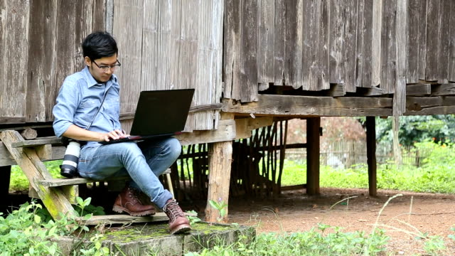 young man working with laptop computer and camera in rural of thailand. - hut stock videos and b-roll footage