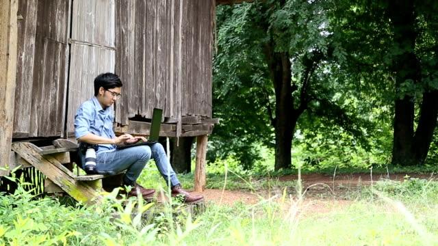 若い男は、ラップトップ コンピューターと農村でのカメラ操作します。