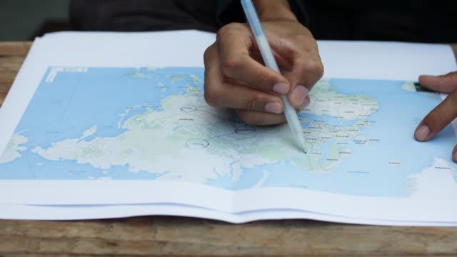 vidéos et rushes de jeune homme écrivant cercle sur la carte du monde, 4 k (uhd - écrire