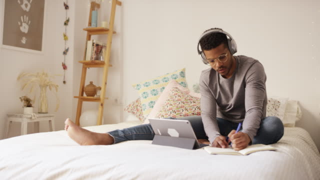 vídeos y material grabado en eventos de stock de joven escribiendo en diario por con tableta digital - afro
