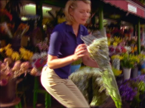 Young man + young woman + senior couple buying flowers from flower store / France