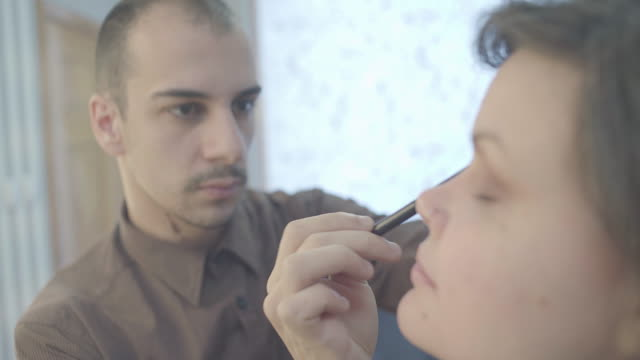 young man,make-up artist,applying blush on young woman's cheek - males stock videos & royalty-free footage