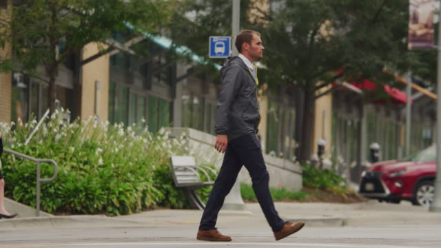 Young man/pedestrian wearing a rain coat crosses an urban street and intersection.