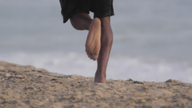 A young manÕs barefoot feet running on the beach. - Slow Motion