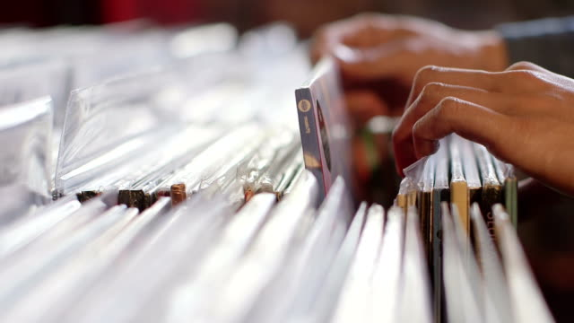 CU A Young Man's fingers flick through a rack of vintage records