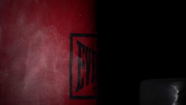 CU Young man's fists punching red punching bag / Orem, Utah, USA