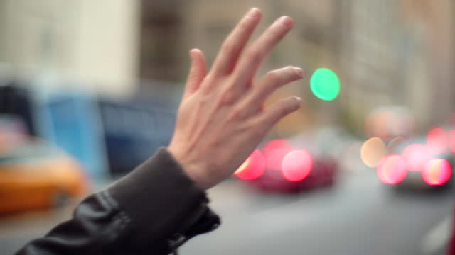 Young man's hand hails taxi-cab on busy city street-corner
