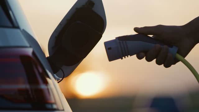 slo mo young man's hand inserting an ev plug into a vehicle inlet for a charging - sustainable energy stock videos & royalty-free footage