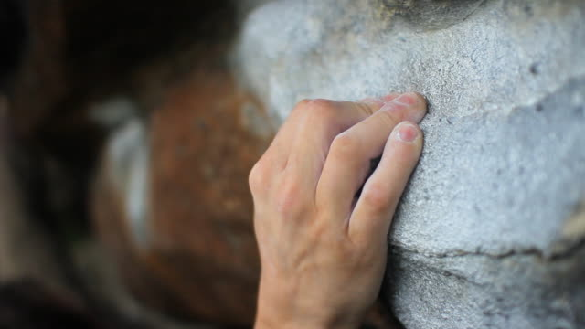 a young manâ??s hands as he is bouldering.  - filmed in hebden bridge, yorkshire, england, europe - roccia video stock e b–roll