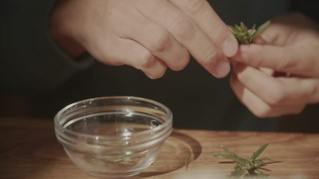 cu young man's hands picking rosemary herb leaves for cooking - ローズマリー点の映像素材/bロール
