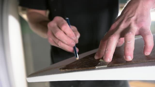 vídeos de stock e filmes b-roll de cu young man's hands working on a surfboard in his workshop - moldar