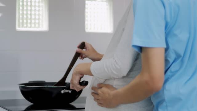 jung verheiratet paar umfasst neben tisch in der küche stehen. mann umarmt seine schwangere frau, legte seine hände auf ihren großen bauch, frau bereitet frühstück. lifestyle, paar in der liebe, glückliche menschen. schwangerschaft/geburt - ehefrau stock-videos und b-roll-filmmaterial
