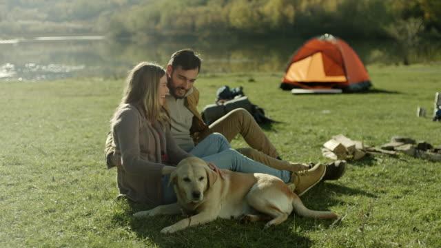 stockvideo's en b-roll-footage met jong getrouwd paar plezier maken met hun hond aan het meer - tent