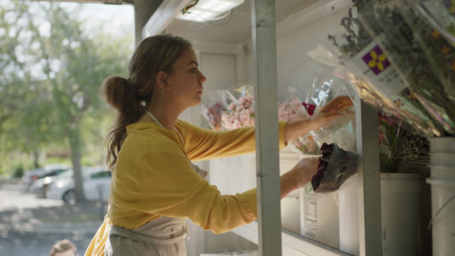 young married entrepreneurs unload fresh flowers from a delivery truck - bukett bildbanksvideor och videomaterial från bakom kulisserna