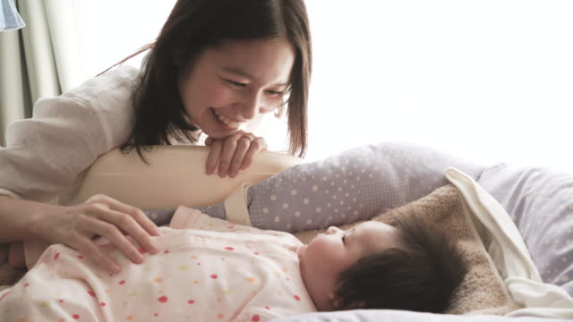 young mather loving her baby girl at home - japanese mom stock videos & royalty-free footage