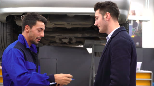 Young mechanic and custumer looking car in auto repair shop