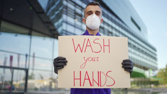 vídeos de stock e filmes b-roll de young medical doctor holding a wash your hands message sign - prontidão