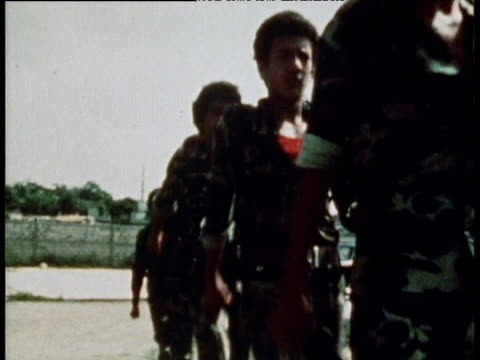 Young men and boys drilling in mismatched uniform with automatic weapons PLO training 1981